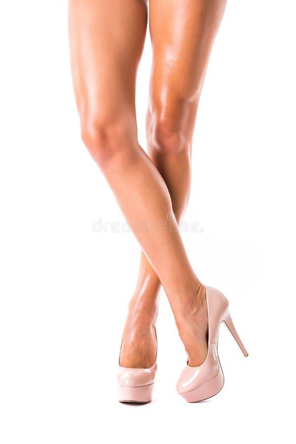Perfectionnez les jambes femelles utilisant des talons hauts d'isolement sur le blanc image stock