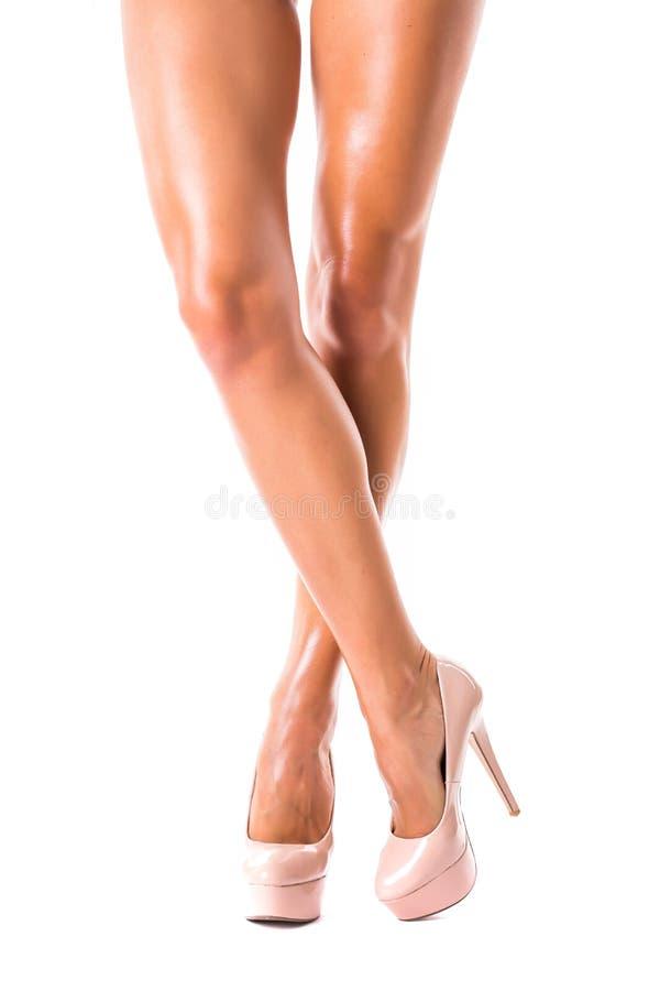 Perfectionnez les jambes femelles utilisant des talons hauts d'isolement sur le blanc images stock