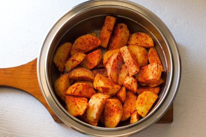 Perfectionnez les pommes de terre rôties avec des épices et des herbes sur le conseil en bois photographie stock