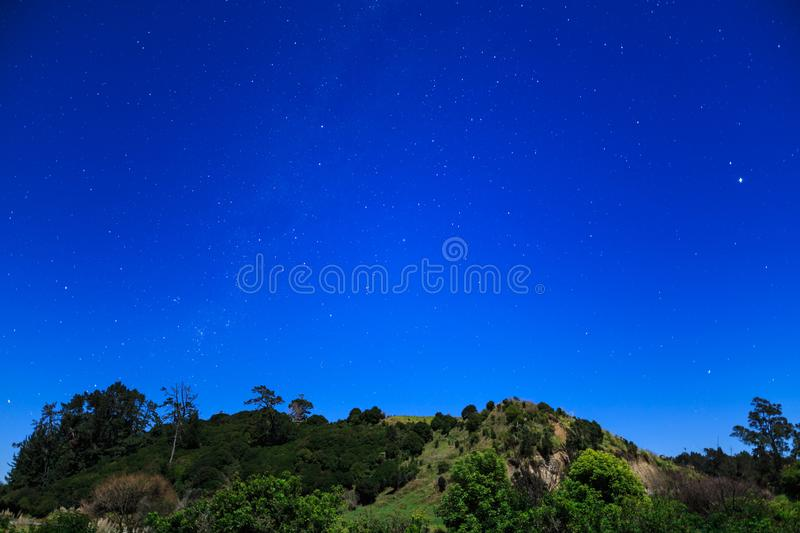 Star-filled sky and moonlit hill in the Southern Hemisphere royalty free stock images