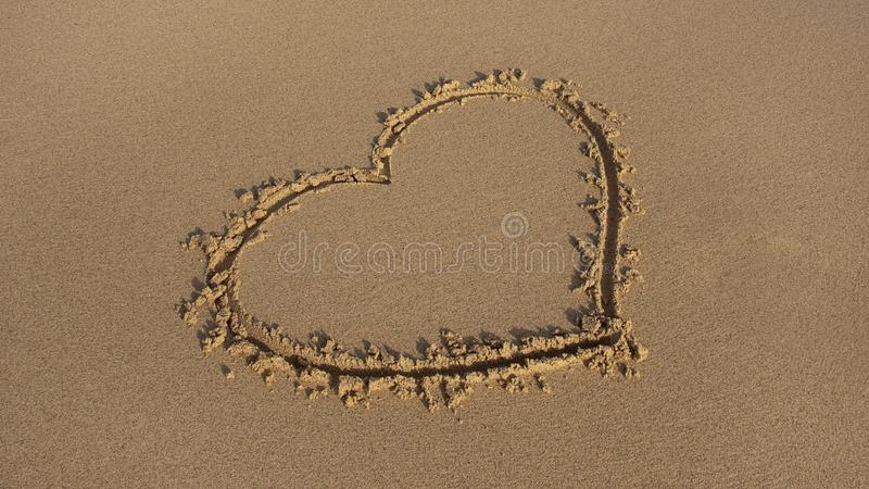 Perfectly drawn heart shape in the golden sand on the beach royalty free stock images