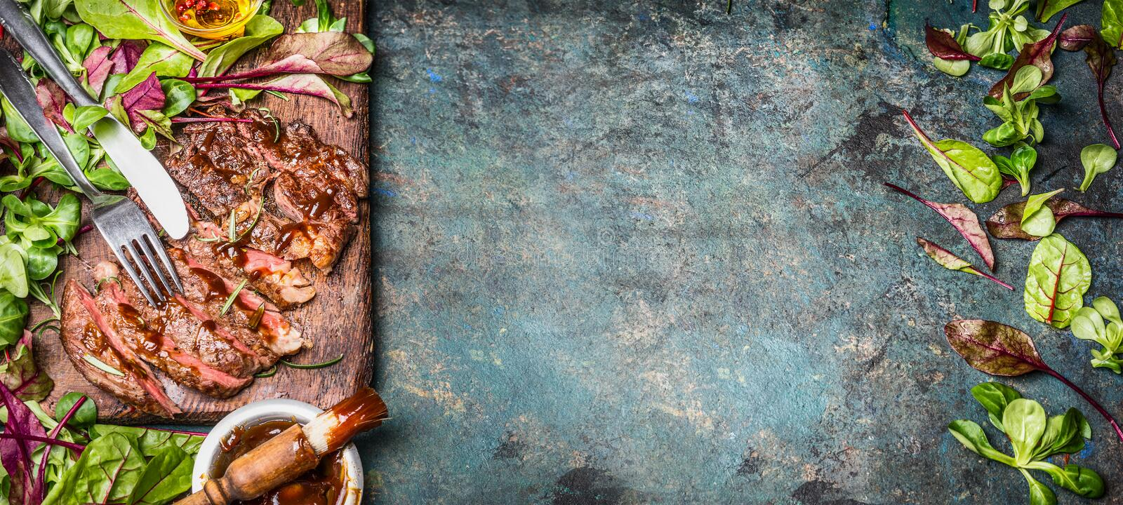 Perfectly fried or grilled steak. Sliced Beef seak , served with green salad leaves and Barbecue sauce on wooden cutting board royalty free stock photography
