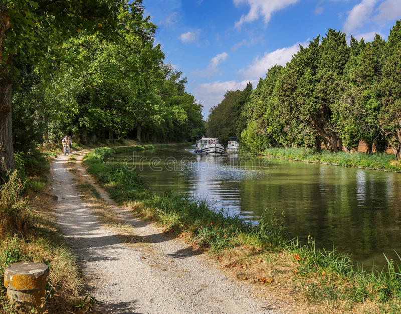 Perfectly scenic on the Canal du Midi in Aude, Languedoc-Roussillon. Image of the footpath with cyclists and the canal with boats lovely summers day on the Canal stock photography