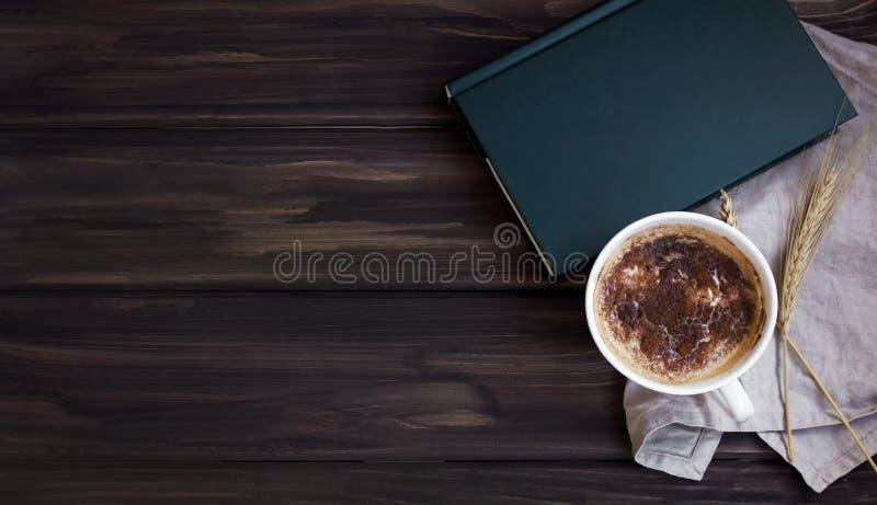Perfekt avbrott med en bok och ett kaffe åt sidan royaltyfri bild