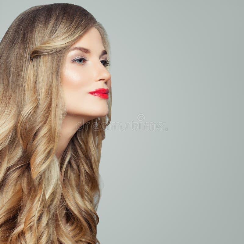 Perfekt blond modell Ursnygg kvinna med långt sunt lockigt hår och röd kantmakeup Ansikts- behandling, haircare och cosmetology arkivbild