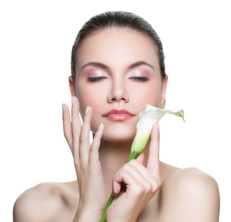Perfekt brunnsortmodell för ung kvinna som isoleras på vit bakgrund Härlig kvinnlig framsida med sund hud och blomma i hennes han royaltyfria foton