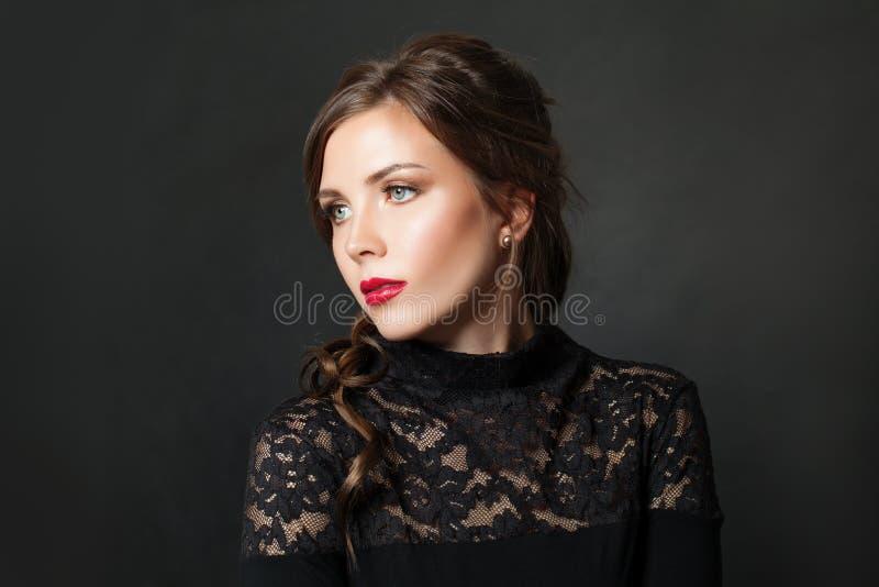 Perfekt elegant kvinna med rött kantmakeuphår på svart bakgrund royaltyfria foton