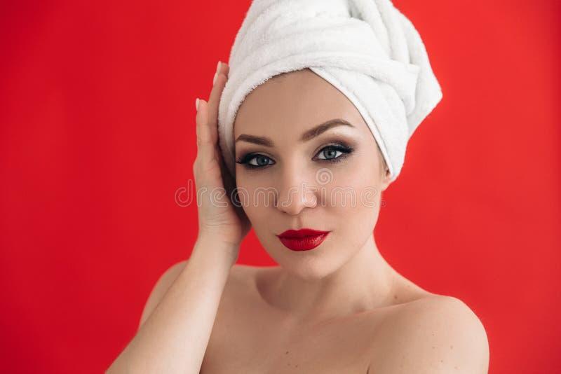 Perfekt flicka med ett härligt smink och röda kanter Närbildstående av en gullig flicka med en vit handduk på hennes huvud royaltyfri fotografi