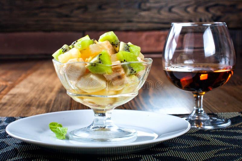 Perfekt fruktsallad med ett exponeringsglas av vin Färgrik sommardesse royaltyfri foto