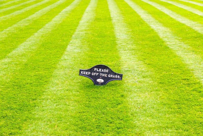 Perfekt gjord randig nytt mejad trädgårds- gräsmatta med ett varningstecken arkivfoto