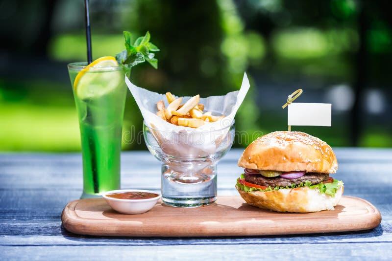 Perfekt kötthamburgare med franska småfiskar och ny kall lemonad På skärbrädan och grön sommarbakgrund royaltyfri fotografi