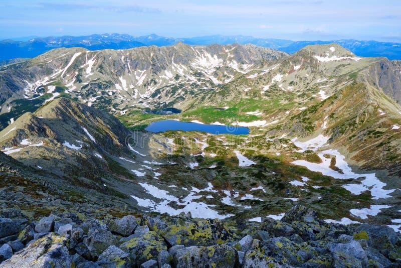 Perfekt klar sjö Bucura 2040m, en glaciärcirquesjö i Retezat berg, Rumänien, som sett från det Peleaga maximumet, på soluppgång arkivfoto