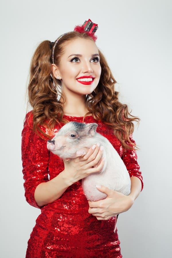 Perfekt kvinna med makeup som rymmer det mini- svinet, modestående royaltyfria foton