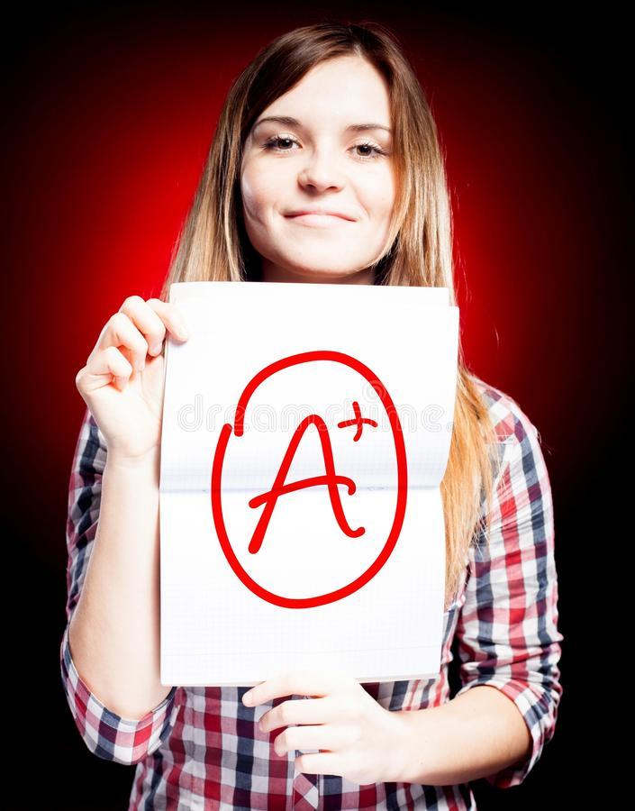 Perfekt plus för skolakvalitet A av examen och den lyckliga flickan royaltyfri fotografi