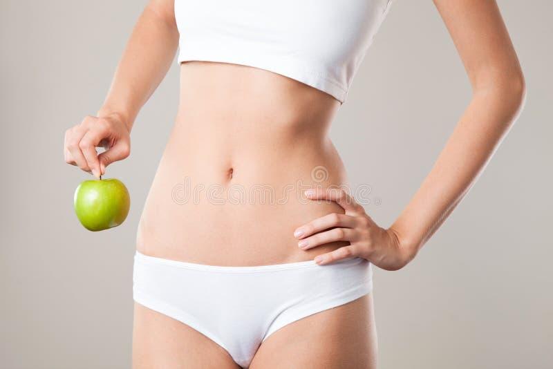 Perfekt slankt kvinnakropp och äpple. Banta begreppet arkivfoto