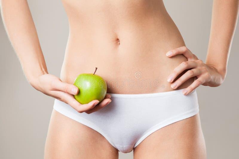 Perfekt slankt kvinnakropp och äpple. Banta begreppet arkivbilder