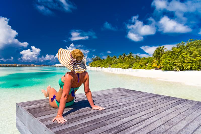 Perfekt strandsemester för sommarloppbakgrund Bärande solhatt och bikini för avkopplad kvinna på palmträd med det blåa havet royaltyfria bilder