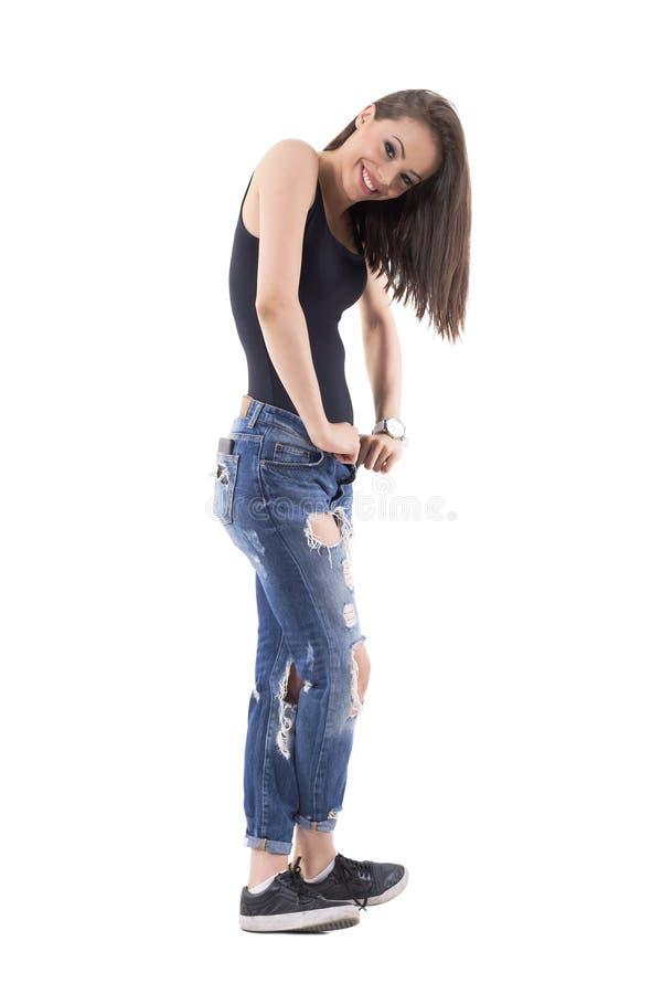 Perfekt ung brunett i riven sönder jeans och svart bästa posera Slapp fokus royaltyfria foton