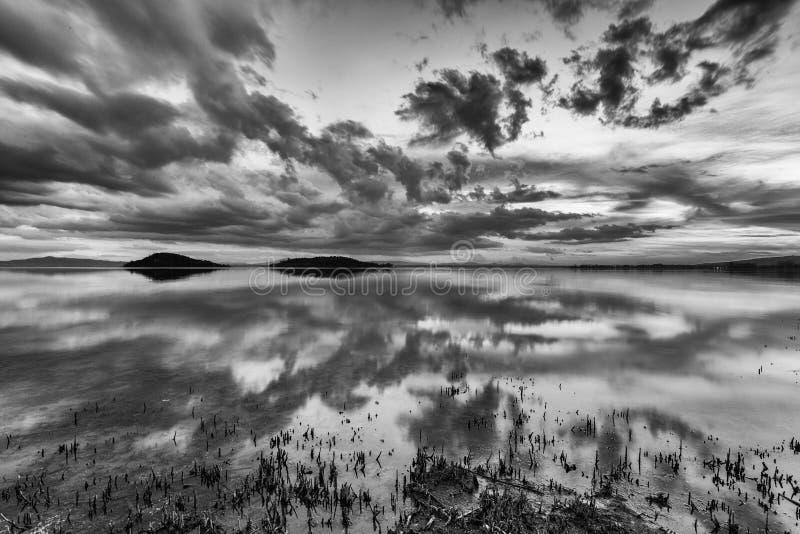 Perfekta och symmetriska moln och öreflexioner på en sjö som gör abstrakta former arkivfoton