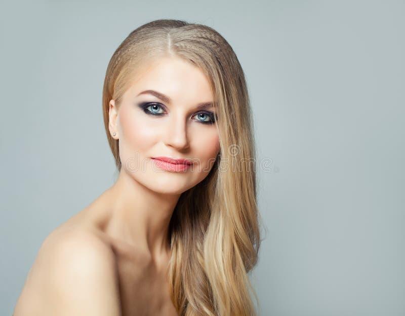 Perfekte Blondine mit dem langen gesunden Haar und klarer Haut Gesichtsbehandlungs-, Haarpflege- und Cosmetologykonzept lizenzfreie stockfotografie