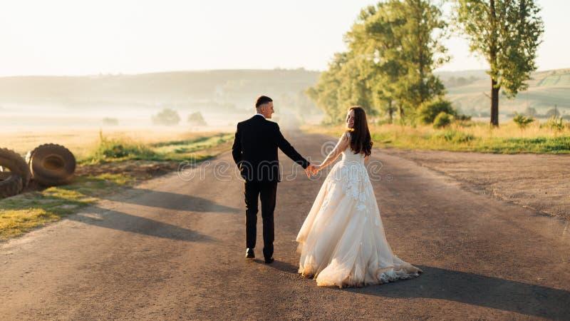 Perfekte Braut schaut über ihrer Schulter beim Gehen mit Bräutigam stockfotos