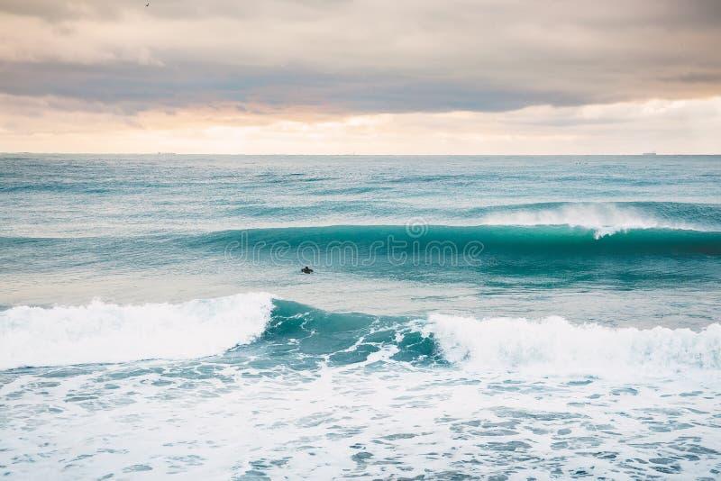 Perfekte große brechende Ozeanfasswelle und alleinsurfer lizenzfreies stockfoto