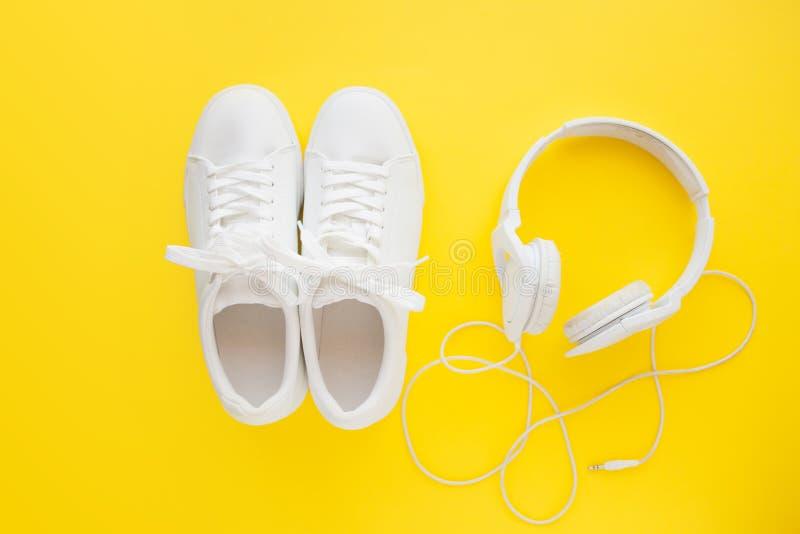 Perfekte weiße neue Turnschuhe, die auf einem hellen gelben Hintergrund nah zu den weißen Kopfhörern stehen stockfoto