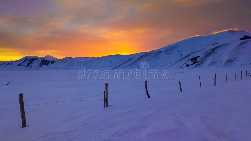 Perfekter brennender Sonnenuntergang in der winterlichen Landschaft mit Schnee lizenzfreies stockbild