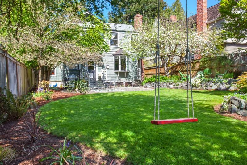 Perfekter Hinterhof mit Baumschwingen und -gras stockfoto