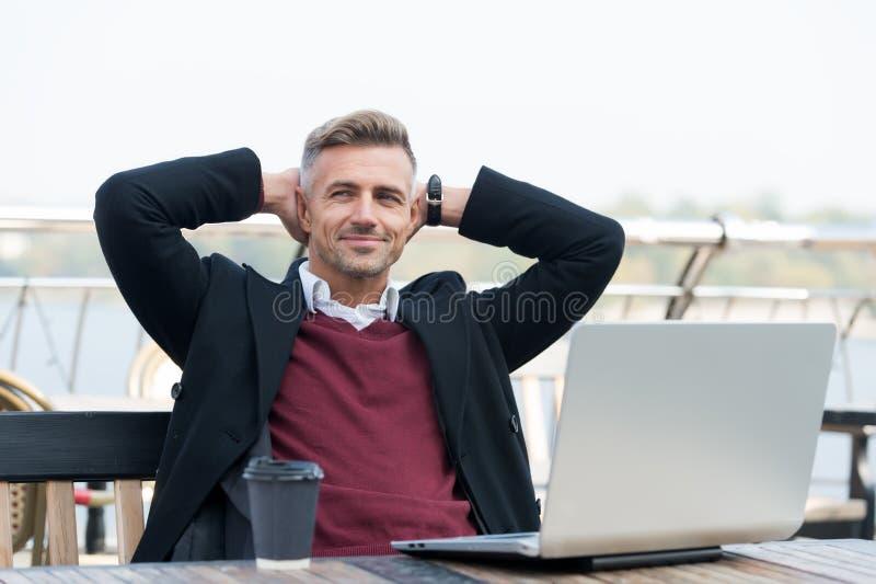 Perfekter Morgen Hübscher lächelnder Mann, der seinen Kaffee genießt Happy hipster mit Laptop und Kaffeetasse Terrasse stockfotos
