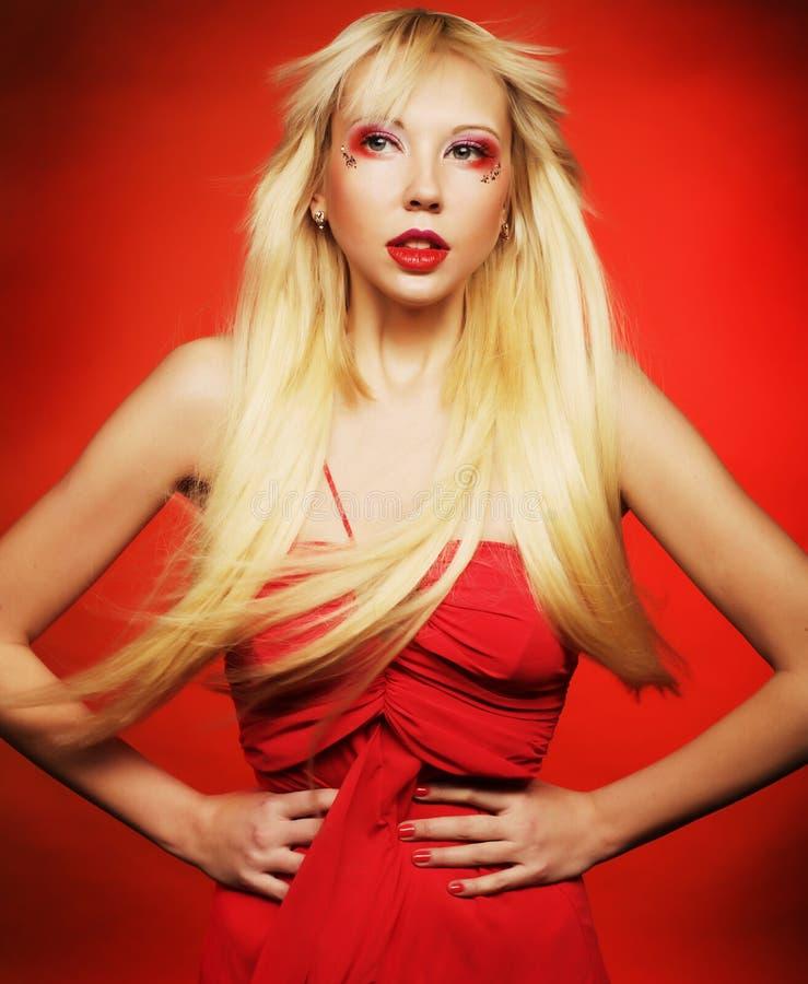 Perfektes blondes Modell im roten Kleid über rotem Hintergrund stockbilder