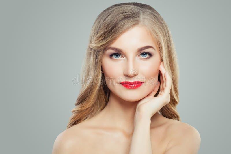 Perfektes blondes weibliches Modell mit Make-up, dem langen gesunden gelockten Haar und klarer Haut Gesichtsbehandlung, Haarpfleg lizenzfreie stockfotos