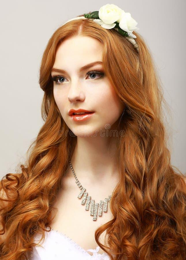 Perfezione. Donna dorata felice dei capelli con il fiore. Femminilità & sensualità immagini stock