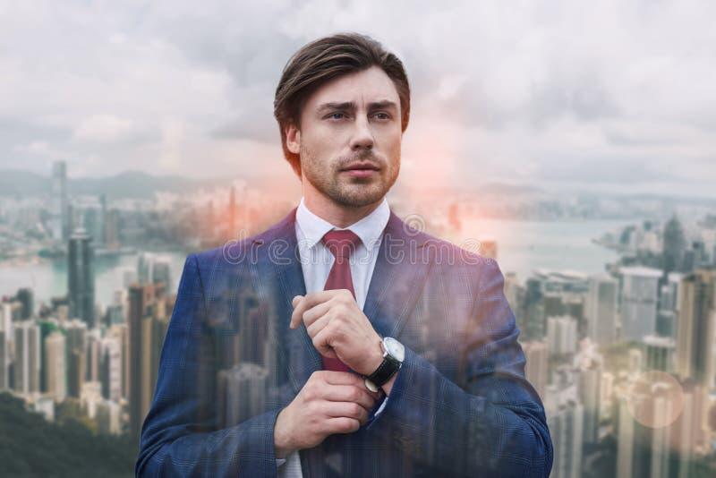 Perfezioni all'ultimo dettaglio Uomo d'affari attraente ed alla moda che regola la sua manica mentre stando contro del paesaggio  fotografia stock libera da diritti
