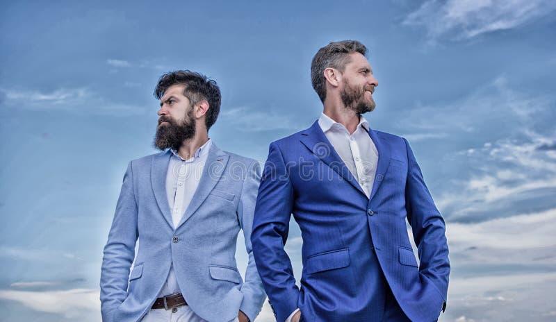 Perfezioni in dettaglio ogni Gli uomini di affari stanno il fondo del cielo blu Gente di affari di concetto Aspetto ben curato fotografia stock libera da diritti