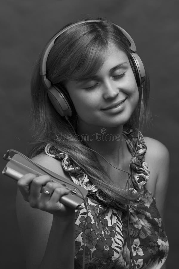 Perfil blanco y negro de una muchacha hermosa joven que escucha la música en los auriculares fotografía de archivo