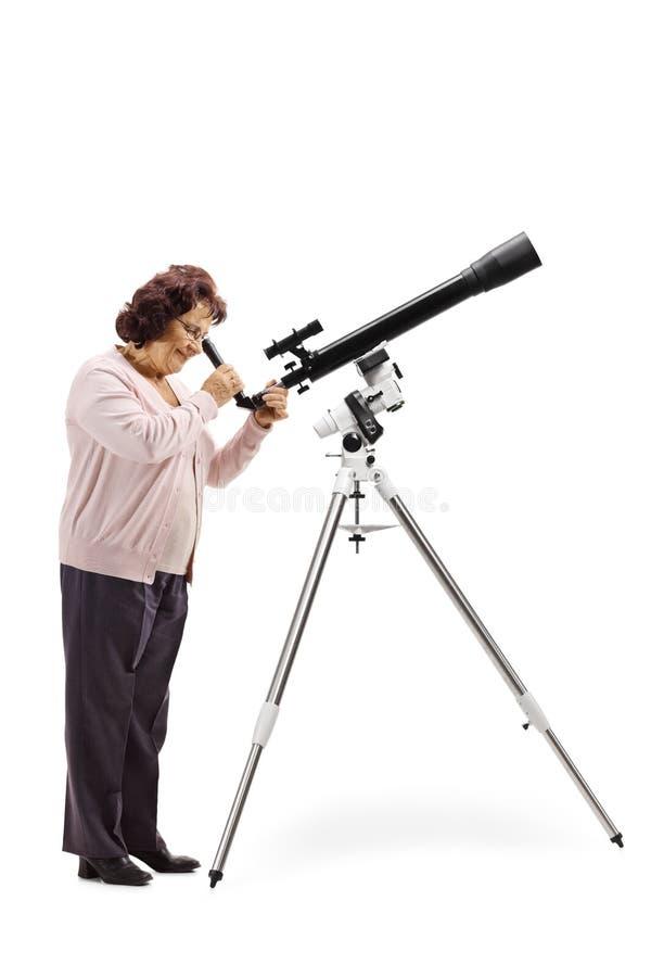 Perfil completo do comprimento disparado de uma mulher idosa que olha através de um telescópio fotografia de stock royalty free