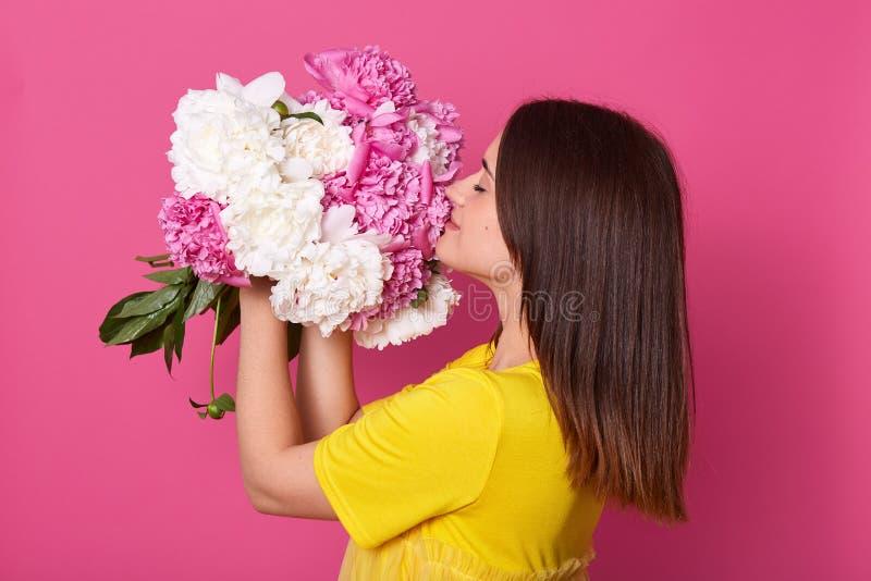 Perfil da fêmea bonito bonita macia que guarda flores em ambas as mãos, fechando seus olhos, aumentando as peônias brancas e cor- imagem de stock royalty free
