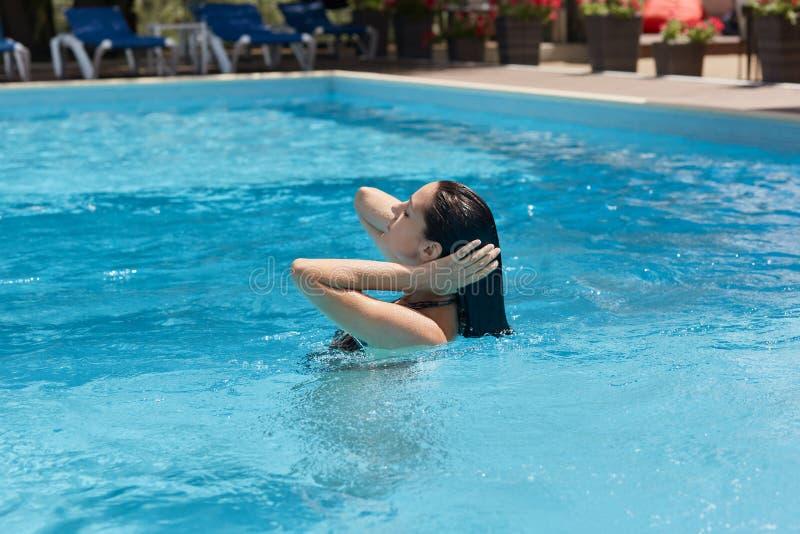 Perfil da jovem mulher graciosa de cabelo preta que nada na piscina, passando o tempo no spa resort luxuoso do hotel, tocando nel imagem de stock