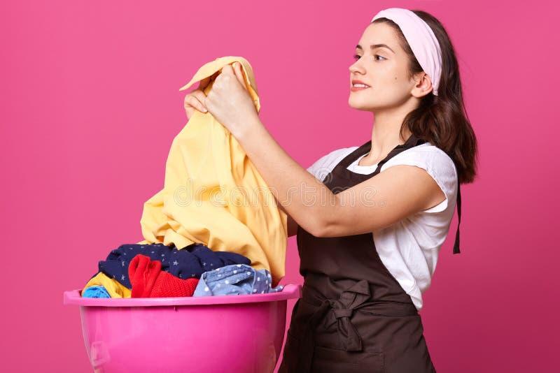 Perfil da morena atrativa deleitada que guarda a camisa leve após o lavagem, sendo satisfeito com o resultado, sorrindo sincerame foto de stock royalty free
