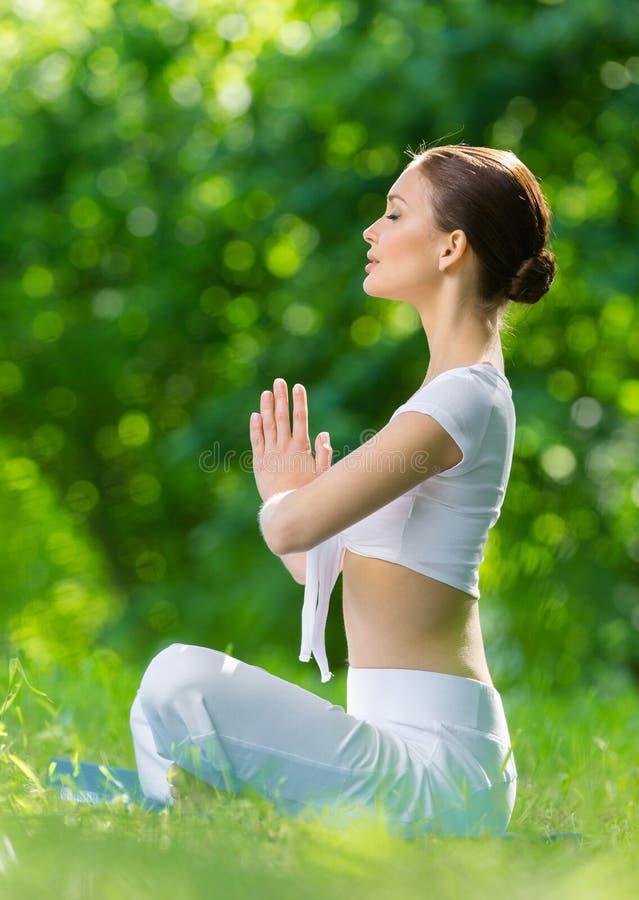 Perfil da mulher em gesticular da oração da posição de lótus fotos de stock