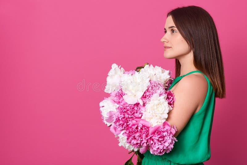 Perfil da mulher europeia atrativa pensativa que olha direta, guardando as flores, estando isoladas sobre o fundo cor-de-rosa imagem de stock