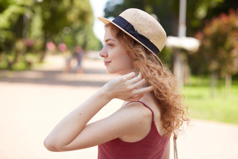 Perfil de la hembra joven atractiva romántica europea que mira a un lado, tocando su pelo con los fingeres, el sombrero de paja q imagenes de archivo