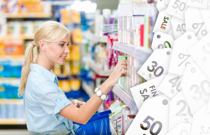 Perfil de la muchacha en la tienda que elige los cosméticos Liquidación fotos de archivo libres de regalías