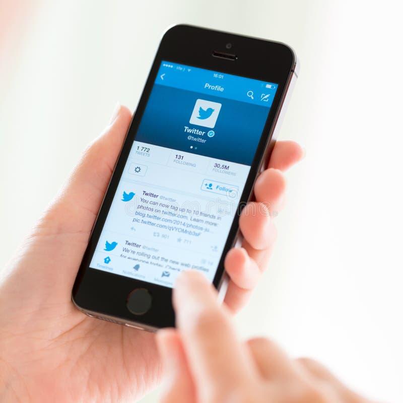 Perfil de Twitter en el iPhone 5S de Apple foto de archivo libre de regalías