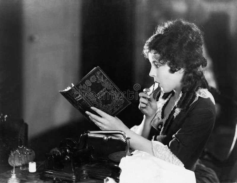 Perfil de um assento da jovem mulher e leitura um livro e comer (todas as pessoas descritas não são umas vivas mais longo e nenhu foto de stock