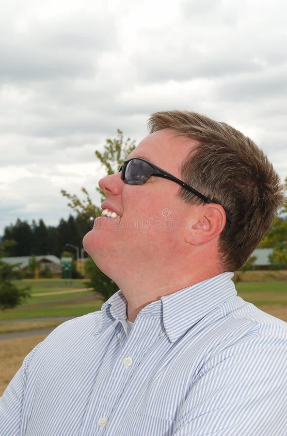 Perfil de um homem novo feliz nos óculos de sol. imagens de stock royalty free