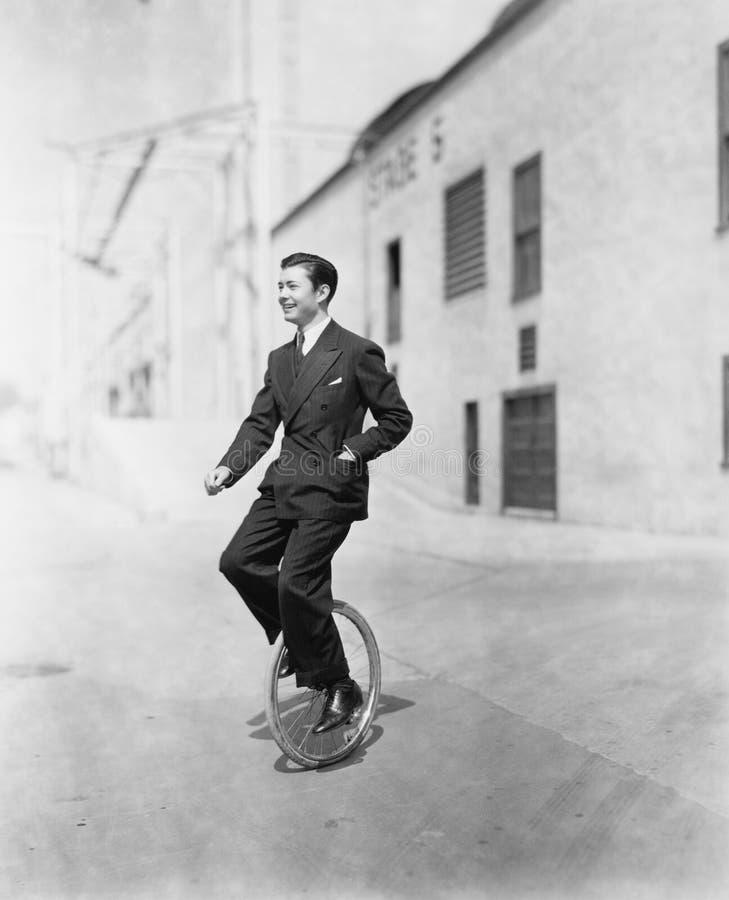 Perfil de um homem novo que monta um unicycle (todas as pessoas descritas não são umas vivas mais longo e nenhuma propriedade exi fotos de stock