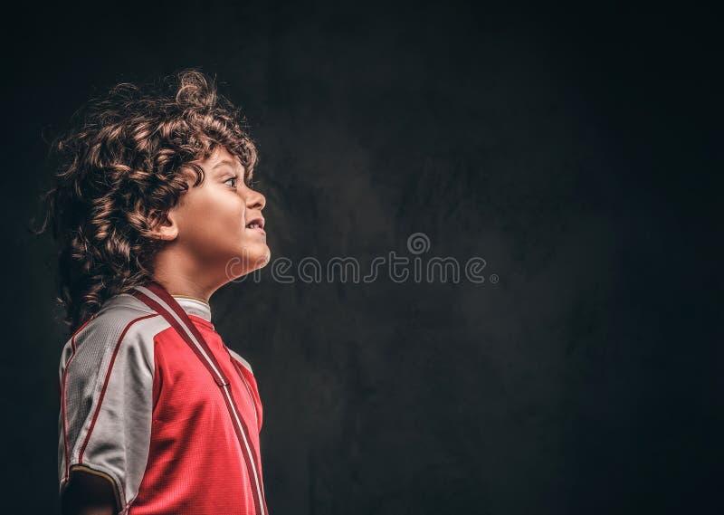 Perfil de um menino pequeno bonito do campeão no sportswear com a medalha de ouro no fundo textured escuro fotos de stock royalty free