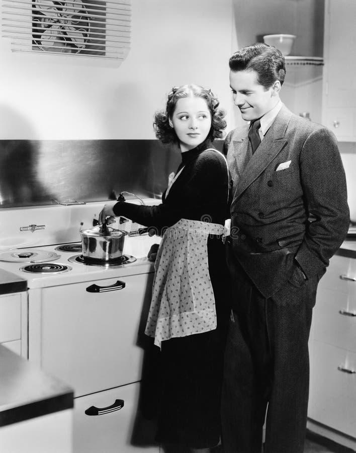 Perfil de uma jovem mulher que cozinha o alimento com um homem novo (todas as pessoas descritas não são umas vivas mais longo e n fotos de stock royalty free